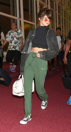Selena Gomez street style - forest green joggers, black crop top, distressed jeans jacket, converse
