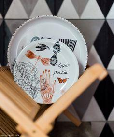 Pratos da artista Calu Fontes e painel de ladrilho hidráulico ao fundo.
