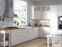 IKEA Traditional kitchen with white cabinets, wood worktops, glass doors and integrated appliances