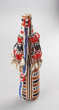 Bottle; made of European blue glass; bottle covered with multi-coloured beadwork; carved wooden stopper attached to bottle with beadwork, decorated with multicoloured beadwork and tassles hanging down from stopper with cowrie shells on end of each tassle, orange bead sewn onto end of stopper that inserts inside bottle.