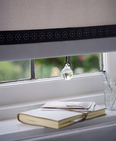 Roller blind with added trim - lace or ribbon - and a decorative pull.