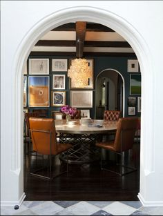 this dining room has such a cool vibe.  The smoky blue color of the wall plays off the camel-color leather chairs.  The table itself is cool w/the round, unique base.  The light fixture hanging from those beautiful wood beams & framed by that perfect arch is really the star though....