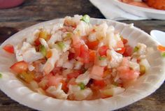 CONCH SALAD is a Bahamian dish that can serve as an appetizer or a meal, like most salads. The conch is fresh-taken from its shell and cleaned. The eye is removed. It is then cut into bite-sized pieces. It is mixed with diced green pepper, onion, and tomato, and dumped into a bowl. Then, lime or lemon juice is squeezed over it along with orange juice until the bowl is full of yummy juice. It's then further seasoned with salt to taste. Pepper can be added (and usually is). YUM YUM YUM!