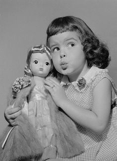 A Terri Lee doll with a silver-blue mink coat, sold at a staggering retail price of $295 at the time of its release, with child model on exhibition at the Toy Guidance Council, United States, 1954, by Terri Lee Doll Company.