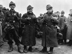 Three 14 year-old German prisoners of war eating rations in front of a group of other POWs, 29 March 1945. The boys were captured by 6th Armoured Division, Third US Army, near Frankfurt-am-Main.