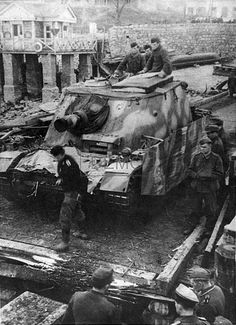 A Sturmpanzer IV 'Brummbar' moving over a bridge while assigned to support ground troops