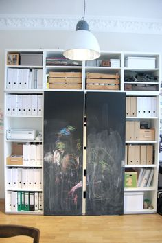 Besta from Ikea along with sliding rails (that are actually meant for shorter doors) and two doors painted with chalkboard paint MDF.