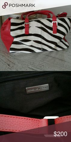 Zebra printed calf-hair satchel with red Bordering on vintage, authentic Addrienne Vittadini bag. Red leather sides and rolled handles. The body of the bag is zebra printed calf hair. Incredibly soft. Interior has two cell phone pockets and one zippered pouch. This bag has been kept in a dust bag when not used (bag will come with) and is in VERY good condition. Adrienne Vittadini Bags Satchels