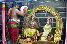 Brahmana priest bathes a Somaskanda (Shiva, Uma and Skanda) deity at temple in Tamil Nadu