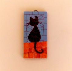 A mosaic wall hanging featuring a cute black cat sitting.The cat figure is made of unglazed ceramic mosaic tiles and the background is made of