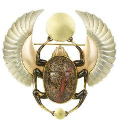 A French Egyptian Revival Art Deco beetle brooch.The brooch in the form of a winged scarab beetle, symbolising the rising sun, with oval carved hardstone body and three pairs of legs, the front and back legs clasping circular yellow gold plaques of differing sizes, the outspread wings of rose and white gold, all in 14 carat gold with brooch fitting, circa 1925.