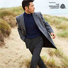 Man wearing wool coat, wool jumper and wool trousers in sand dunes