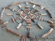 Mandala Art Medium: ~~rounded speckled drift wood, grey stone, dark and light driftwood pieces, driftwood stick on a white sand canvas~~