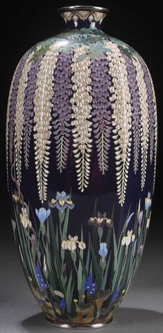 A VERY FINE JAPANESE CLOISONNÉ ENAMELED BRONZE AND SILVER MOUNTED VASE, HAYASHI KODENJI WORKSHOP, MEJI PERIOD, CIRCA 1890. Of ovoid six panel form, decorated with cascading wisteria above irises on a midnight blue ground, signed with incised chop mark on base. Height 9.5 inches (24 cm).