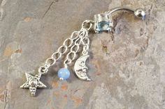 Blue moon belly and star button jewelry ring on a barbell style piercing. The barbell is a standard 14 gauge hypoallergenic surgical steel belly piercing accessory. Moon and star charm are silver plat