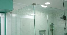 good view of frameless glass shower/tub enclosure and accent tile strip, also new dimable led light fixture over shower/tub.