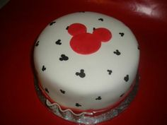 Mickey Mouse Cake - Cakes always look so much better in my head. If I could only get a cleaner finish...... sigh (a girl can dream). This is a strawberry  cake w/cream cheese frosting covered in mmf. I drew the mickey head silhouettes with a food color marker. The big one is red mmf.