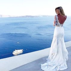 Our lovely #PninaBride @jaclynmisch and the breathtaking views of Santorini, Greece! Tag a girlfriend that would say YES to this beautiful lace #PninaTornai gown.