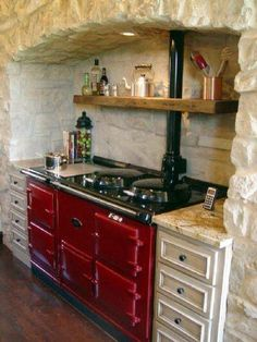 A red Aga stove would be in my dream kitchen. Love the 'hearthlike' feel of the way this is set into stone. Aga Kitchen, Farmhouse Kitchen Cabinets, Cottage Kitchens, Country Kitchen, Home Kitchens, Kitchen Dining, Kitchen Decor, Nice Kitchen, Kitchen Chairs