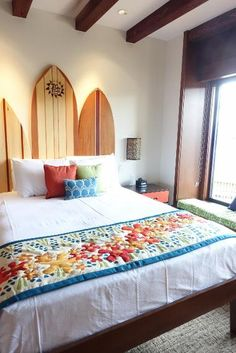 One of the colorful bedrooms in the bungalow has a headboard made of surfboards.