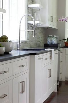 Modern pulls on white cabinets. Milton Development: Contemporary kitchen design with white inset kitchen cabinets paired with black granite ...