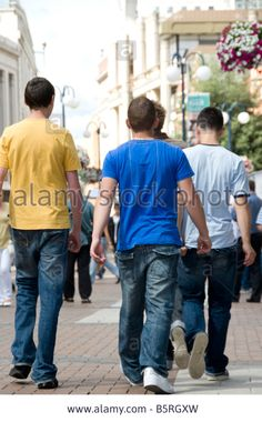 Back View Of Teenage Boy Walking Down The Street With Teenage Boys ...