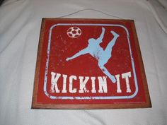 """Kickin It Soccer Boys Sports Bedroom Wooden Wall Art Sign by The Little Store Of Home Decor. $19.99. size 13x13; made in the USA. We've sealed this Kickin It Soccer print onto wood giving it a framed appearance. The background wood is painted a chocolate brown color with touches of black to accent the print. It measures approximately 13"""" squared by 1/4"""" thick (wood dimensions not including hanger). We've added a rusty tin wire for easy hanging. Lots more sports deco..."""