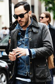 Shop this look for $98: http://lookastic.com/men/looks/military-jacket-and-denim-jacket-and-crew-neck-sweater-and-longsleeve-shirt-and-jeans/775 — Charcoal Military Jacket — Blue Denim Jacket — Navy Crew-neck Sweater — White Longsleeve Shirt — Navy Jeans
