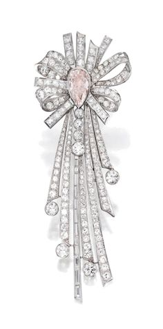 PLATINUM, DIAMOND AND COLORED DIAMOND BROOCH The stylized ribbon bow centered by a pear-shaped Faint Pink diamond weighing 2.02 carats, accented by baguette and French-cut diamonds weighing approximately 2.80 carats, further set with numerous old European and single-cut diamonds weighing approximately 7.25 carats.
