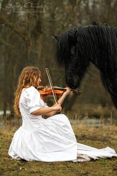 Playing violin in a beautiful dress with a magnificent Freshen coming to listen and see the beauty of music.