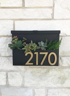 Welcome Home. Create instant curb appeal with this unique mailbox with planter box for seasonal flowers or colorful succulents and sleek magnetic aluminum address numbers! This mailbox is made to order in Austin, TX and is constructed of 14 gauge steel. The mailbox floats about a quarter inch off