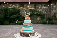 Colorful, 4-tier wedding cake- white cake with orange and teal accents, with unique pennant banner, and unique cake stand. Willowdale Estate is a weddings and events venue on the North Shore. Willowdaleestate.com