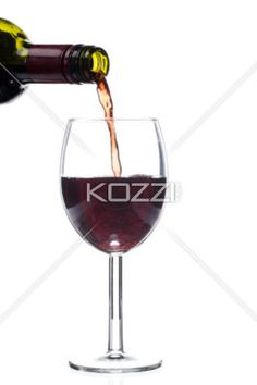 wine bottle pouring wine in glass. - Close-up cropped shot of wine bottle pouring red wine in wineglass against white background.