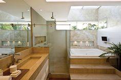 Nesta sala de banho no Rio de Janeiro, a claraboia de vidrono teto deixa o sol entrar. No alto também existe um rasgoiluminado por fluorescentes (não aparece na foto). As dicroicas, sobre a bancadade travertino, facilitam a maquiagem, enquanto as lâmpadasPAR 20, no teto do boxe, resistem melhor à umidade. O nichoda banheira tem minidicroicas, ideais para áreas reduzidas.