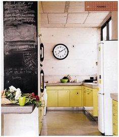 Concrete countertops on metal cabinets. Nice industrial look without being too heavy thanks to the natural light & bright color. The chalk board wall is also a nice touch.