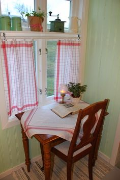 Perfect morning spot. Wood table with red trimmed tablecloth, in front of a red curtained window. So refreshing to see color and wood instead of all white.