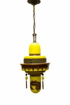 Glazen Hanglamp. Oranje-geel glas gedecoreerd met bruin glazen tekening in sierrand en bloemen. Zie ook de mooie bruin gepatineerde koperen rand over het glas, dit is het aanhechtingspunt van de 2 kappen die over elkaar vallen en die je moet openen om de lamp te vervangen. Ook de gebruikte kralen aan de zijkant van de lamp zijn van glas. Prachige sierlamp voor sfeerverlichting uit de jaren 20.