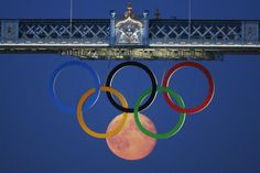 The full moon rises through the Olympic Rings hanging beneath Tower Bridge during the London 2012 Olympic Games Reuters/LUKE MACGREGOR