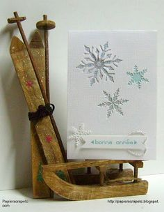 handmade New Year's card from papierscrapetc ... elegantly clean and simple ... three different negative space die cut snowflakes  ... like the design and what looks to be shimmering backing for the snowflakes ... great presentation for the photo too!