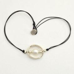Colgante con tira de cuero, abalorios zamak bañados en plata, perla y cierre botón.  PRECIO: 15 €