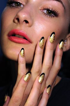 """Norman Ambrose: CND's Manacchio also worked on Norman Ambrose's spring 2012 show during New York Fashion Week. Six different nail looks were used to portray a theme of a glamorous woman """"who swims in her diamonds.""""  Pictured here are nails painted in gold, edged in black, and treated with gold leafing. Models wore other hues and textures ranging from gold to red to nudes. All nail looks incorporated the slender, almond-shaped nail trend"""