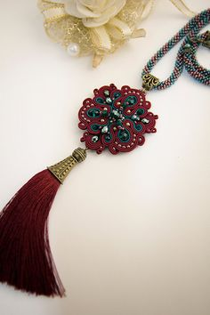 Embroidered tassel necklace Tassel soutache necklace Burgundy tassel necklace Beaded tassel necklace Boho tassel necklace Red tassel pendant   Long handmade burgundy soutache necklace. Embroidered pendant is suspended on a cord woven of the Czech seed beads. I used soutache braid combined with green crystal beads. The back is covered with leather. It can be weared with evening or bohemian casual dresses.  Total length of pendant : 41 cm / 16.14 Total width of pendant: 5 cm / 1.96  -...