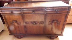 For sale is a Lawrencia Sideboard made from solid wood. It features three cupboards and three draws, the central one being for cutlery. It is of an arts and crafts design, with scrolled draws and a scroll on two of the cupboards. it has ornate floral  panels on front.  and decorative round metal handles.    It shows wear and tear appropriate to age.  Dimensions D 19.5 x  L 53.5 x H  35      Welcome to WeLoveItShop:    We are confidient that you are aware that buying and selling of antiques…