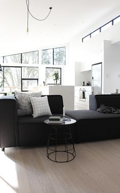 black charcoal modular sofa. black wire side table. elevated angular ceiling.