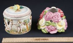 NICE LOT INCLUDES A STUNNING ITALIAN MADE GLAZED POTTERY JAR MEASURING 5 INCHES TALL. IT FEATURES NUMEROUS CHERUBS, IN RELIEF, PLUCKING GRAPES FROM THE VINES. THE LID HAS A FIGURAL PEAR ON TOP. TITLED LA VENDEMMIA WHICH TRANSLATES TO VINTAGE OR HARVEST. NUMBERED 1380. BEARS A HALLMARK OF CIA. THE SECOND PIECE IS A CLUSTER OF PINK, RED AND YELLOW ROSES AND IS A COVER FOR A TEA LIGHT. MEASURES 4 INCHES TALL.