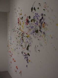"Silk flowers pinned to the wall as if they had been blown by the wind. I""This Way In"", by Jim Hodges."