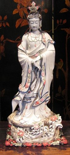 """Glorious Quan Yin ...  Chinese-made porcelain, 24"""" tall. Photo by Lora Fisher. Quan Yin is the Mother Of All Buddhas. Her Tibetan counterpart is the Tibetan Tara. In China, she is the deity to whom women make offerings and prayers for fertility. As such, she is a direct link to prehistoric fertility goddesses. In Tibet, and elsewhere, she is the protectress who guides us through life's endless challenges, and is the granter of all success. –Lora Fisher"""