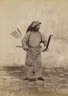 This photo shows a Manchu archer grasping his arrow behind the head with the index finger of the bow hand, while he strokes the feathers on his way to the nock. By feeling the feathers, he knows where the nock is so he can align it to the string without looking. Judging from the round dragon patches on his robe, this archer is of a high noble rank. Manchu nobility was often well trained in their classical fighting arts because they were supposed to serve as an example, circa 1880s to 1890s.