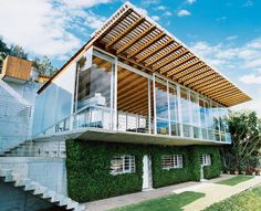 This house has what some architects would call an upside-down plan, with living spaces upstairs and bedrooms below. The upper story is strikingly transparent while the the lower is camouflaged by thick, foliage-covered walls, which keep the sleeping areas cool.