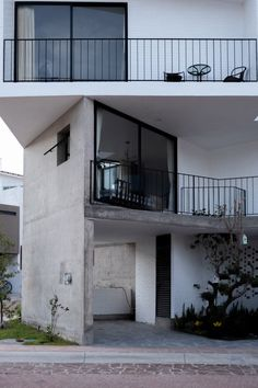 The second and third floors are contained within white brick-covered volumes that are irregularly oriented relative to the ground floor, creating overhangs and terraces within the home's massing. Concrete Structure, Colonial Architecture, Courtyard House, Concrete Design, Interior Garden, Spanish Colonial, Stair Railing, Garden Spaces, White Walls